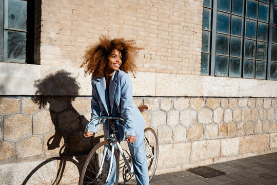 Smiling Afro woman leaning on bicycle while standing by building during sunny day