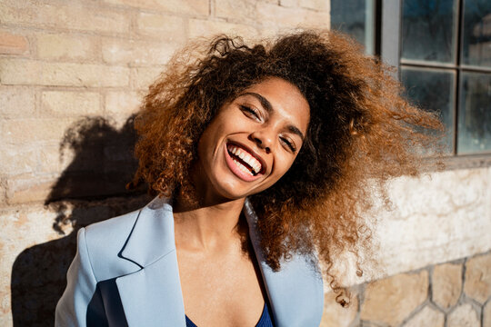 Cheerful Afro woman with brown hair against building