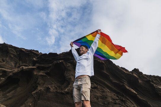 Smiling male tourist waving LGBTQI Flag while standing by rock at El golfo, Lanzarote, Spain