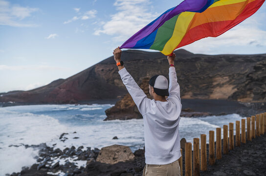 Young male tourist waving rainbow flag while standing at view point El golfo, Lanzarote, Spain
