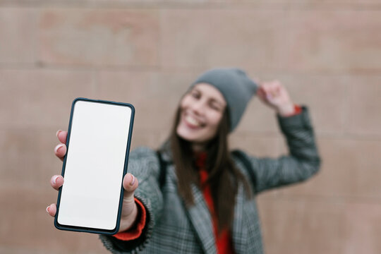 Woman showing blank smart phone screen against wall