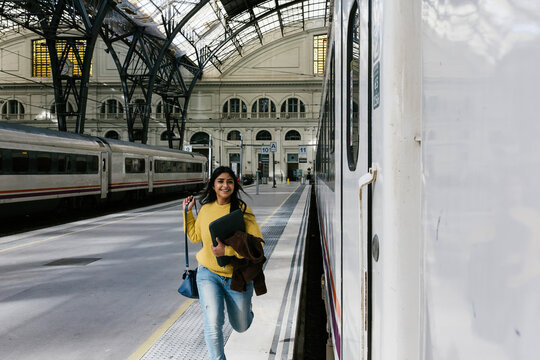Smiling woman with laptop bag running on platform to catch train