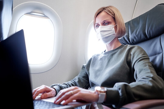 Young woman wearing face mask is traveling on airplane using laptop computer. New normal travel after covid-19 pandemic concept