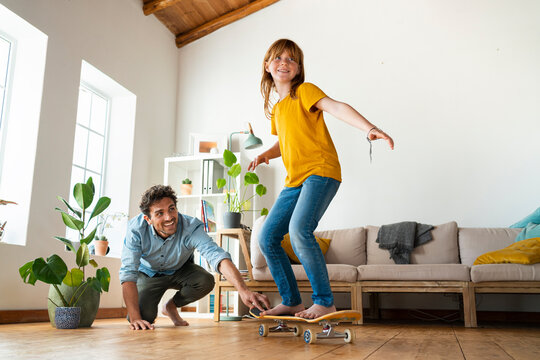 Father helping daughter to ride skateboard in living room at home