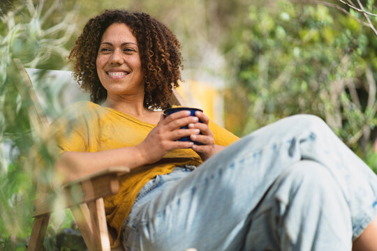 Smiling curly haired woman with coffee cup looking away while sitting on chair in vegetable garden