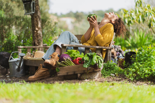 Laughing woman holding fresh broccoli while sitting on bench in garden