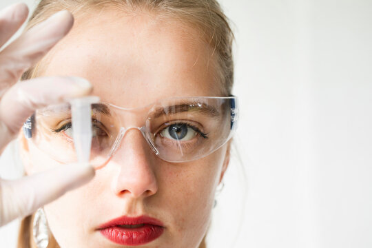 Portrait of beautiful woman wearing protective goggles holding vial