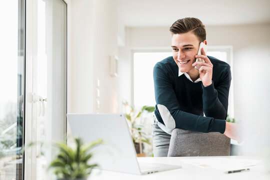 Male entrepreneur talking on phone while leaning on chair at home office