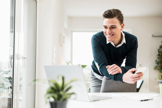 Happy young businessman leaning on chair while looking at laptop in home office