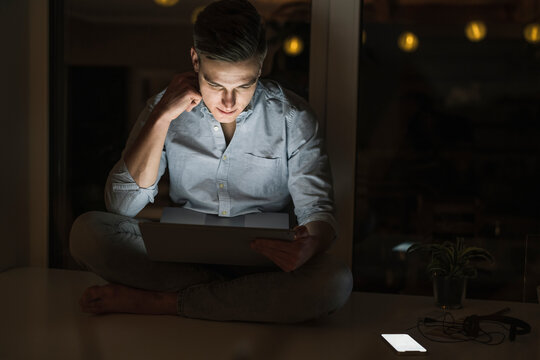 Young male business professional working on laptop while sitting in living room