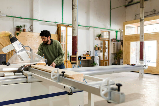 Male carpenter working with table saw in workshop