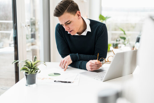 Concentrated male professional reading document while sitting in home office