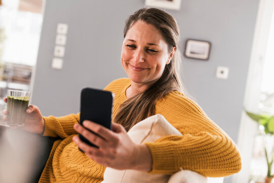 Happy mid adult woman using mobile phone in living room