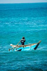 Rybak na kutrze, płynący na otwartym oceanie, kolorowa motorówka na niebieskiej wodzie.