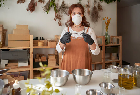 Woman wearing protective face mask holding eyewear during preparation of soap in workshop