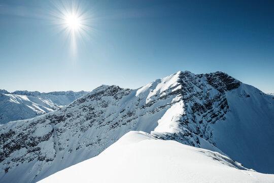 Sunbeam over snowcapped mountain, Lechtal Alps, Tyrol, Austria