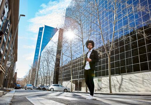 Male entrepreneur holding phone while walking on Zebra crossing against building