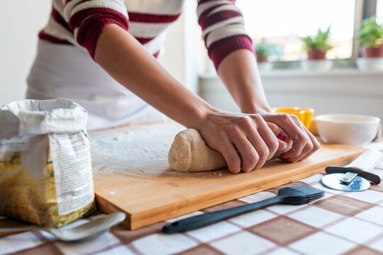 Woman kneading dough for making croissants in kitchen at home