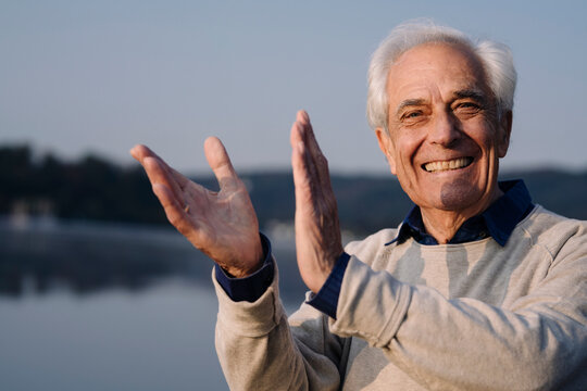 Cheerful man clapping while standing outdoors