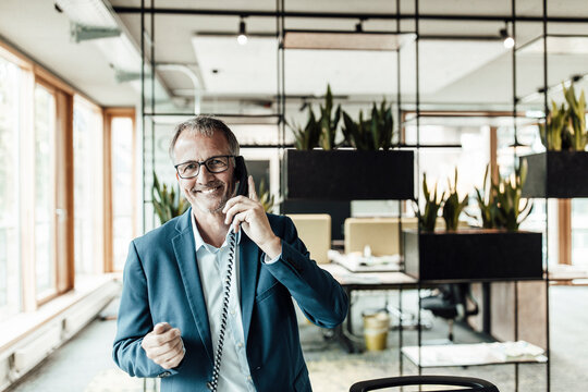 Smiling businessman with eyeglasses talking on telephone while standing in office