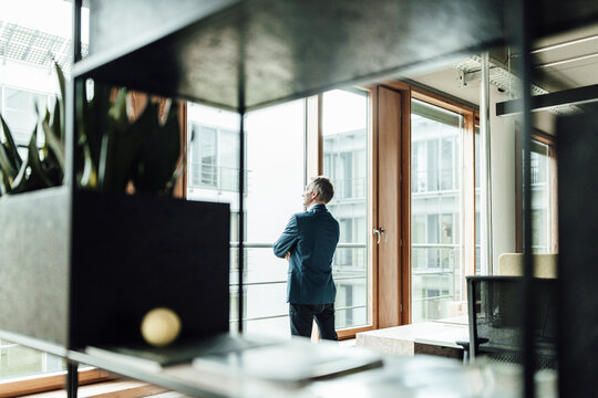 Businessman looking through glass window in office