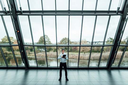 Male entrepreneur using digital tablet while using digital tablet against glass in office corridor