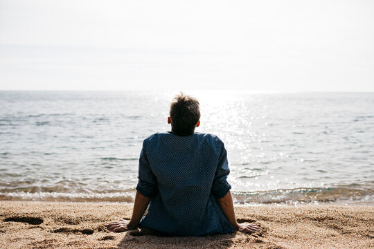 Man relaxing at beach during sunny day