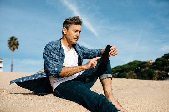 Mature man using mobile phone while sitting at beach during sunny day