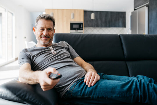 Smiling man holding TV remote while sitting on sofa at living room