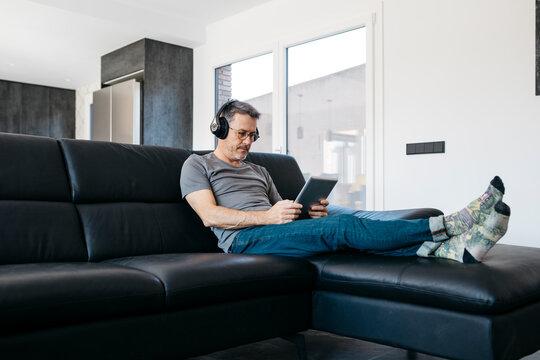 Mature man listening music through headphones while using digital tablet in living room