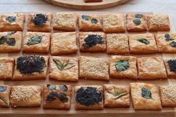 Fototapeta Domowe krakersy ozdobione listkami ziół, sezamem, makiem i solą obraz