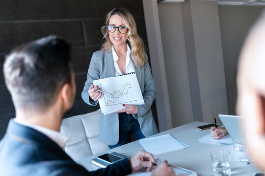 Smiling businesswoman showing graph while standing in office
