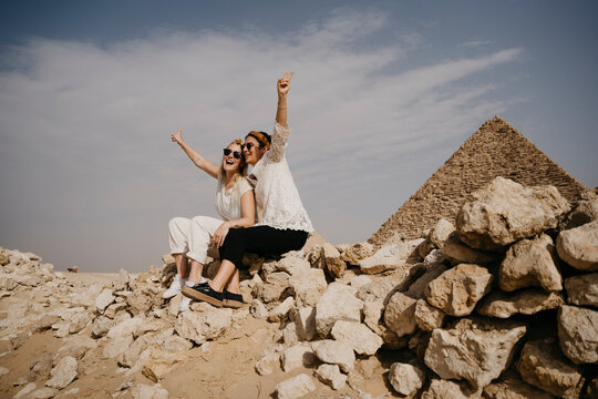 Egypt, Cairo, Two female tourists sitting together on rocks with Great Pyramid of Giza in background