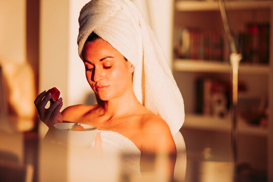 Woman in towel with fruit bowl having strawberry at home