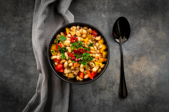 Studio shot of bowl of bean stew with bell and chili peppers, quinoa and parsley