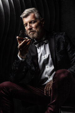 Portrait of a gentleman observing his glass of alcohol