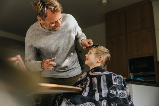 Son laughing with father while getting haircut at home