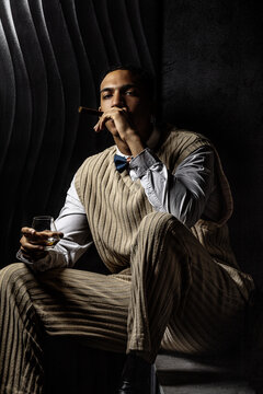 Portrait of a serious young black man smoking a cigar