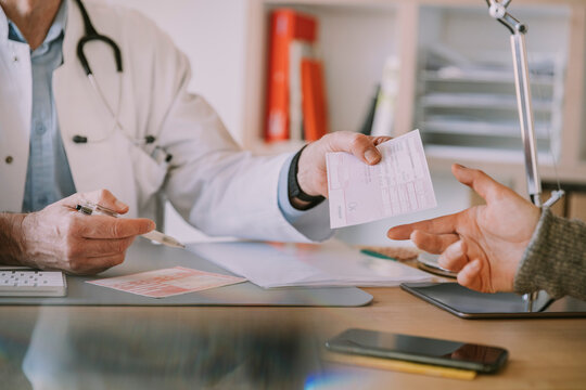 Doctor giving prescription to patient at doctor's office