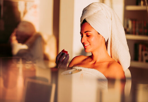 Smiling woman wearing towel eating strawberry at home