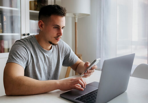 Handsome male entrepreneur with smart phone using laptop on table at home office