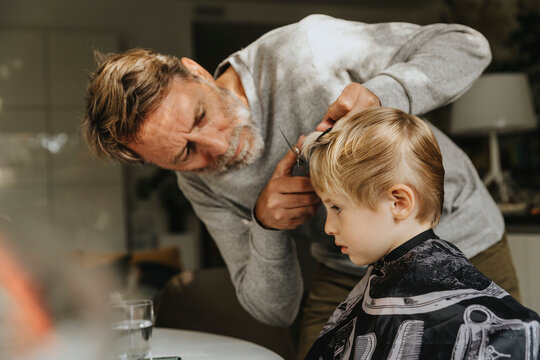 Father doing haircut to son at home