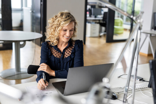 Smiling businesswoman holding pen while looking at laptop in office