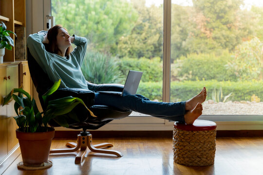 Woman with hands behind head relaxing while sitting with laptop on chair at home
