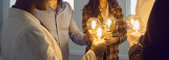 Group of happy young multiracial business people holding electric light bulbs. Team of colleagues join Edison light bulbs as conceptual metaphor for teamwork and sharing ideas in creative community