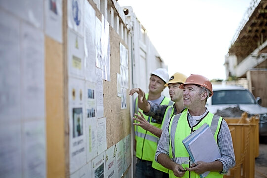 Three male construction workers inspecting bulletin board at construction site