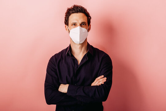 Mid adult businessman wearing FFP2 face mask standing with arms crossed against colored background