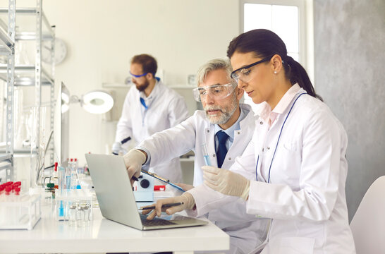Old professor and young scientist with analysis sample working at laboratory discussing test result looking at on laptop screen. Chemistry research, new drug vaccine discovery concept