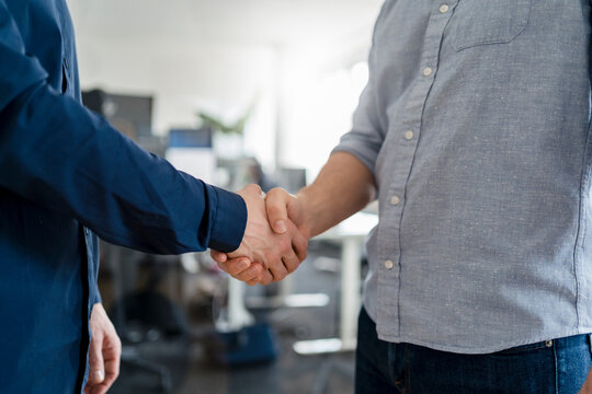 Male entrepreneurs shaking hands at office