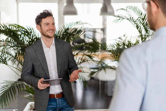 Smiling businessman with digital tablet discussing with male colleague at office